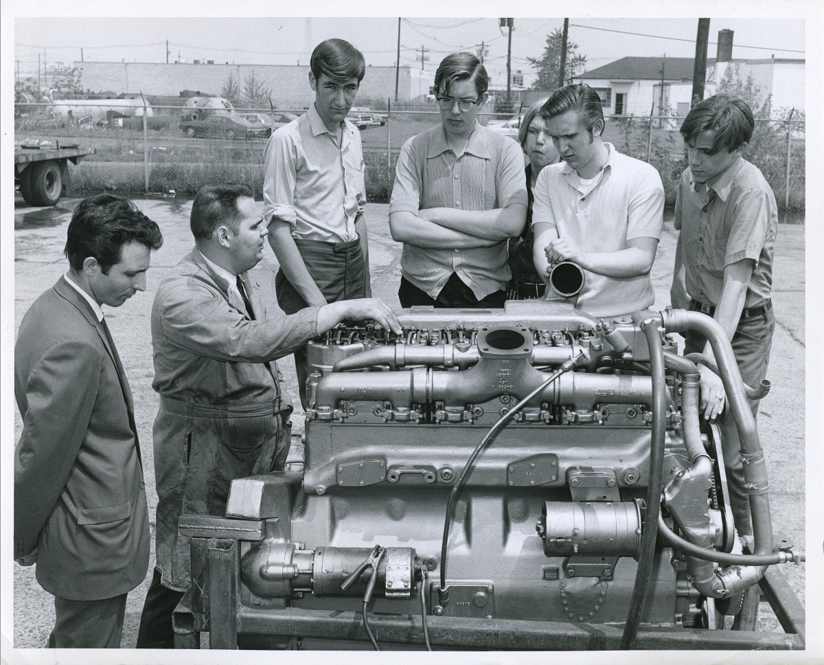 Larry Berlin, surrounded by students, at the Engine City Technical Institute.