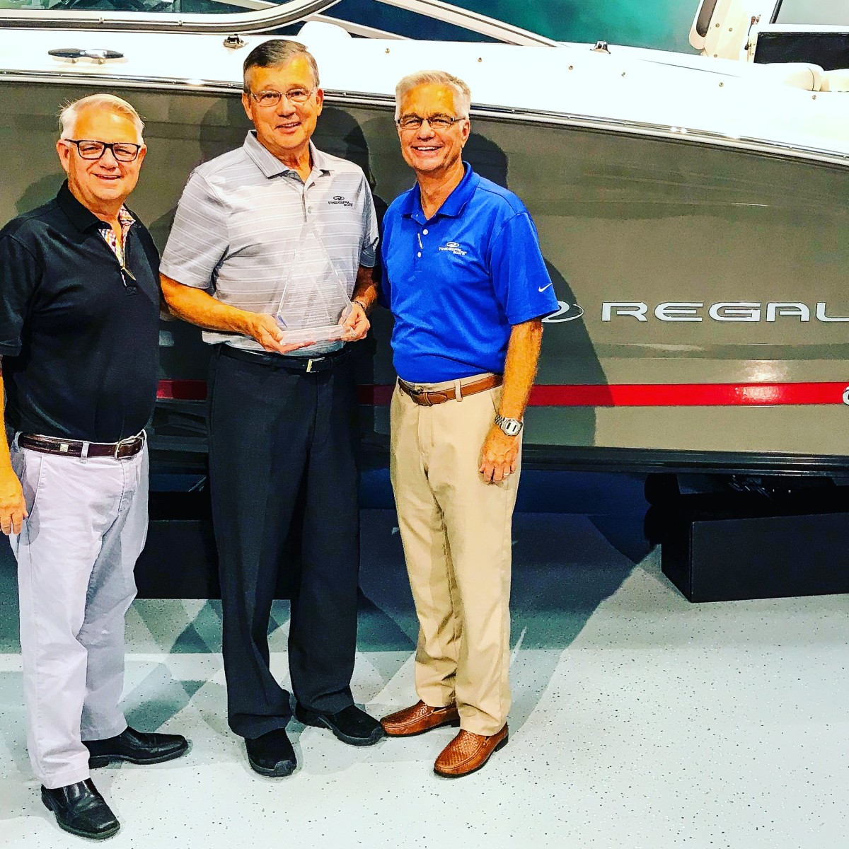 Regal Boats VP Tim Kuck (left) and CEO Duane Kuck (right) present Jim Krueger (center) with a special commemorative crystal award upon his retirement for outstanding leadership.