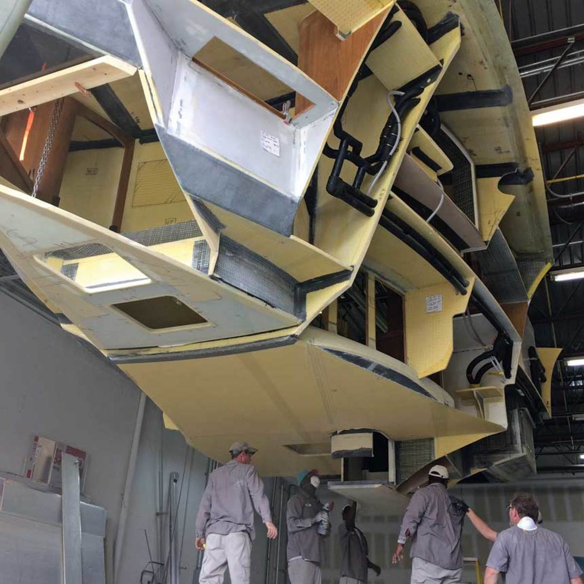 The interior module of a boat is readied to be dropped into the hull.  The yellow panels are infused composite.
