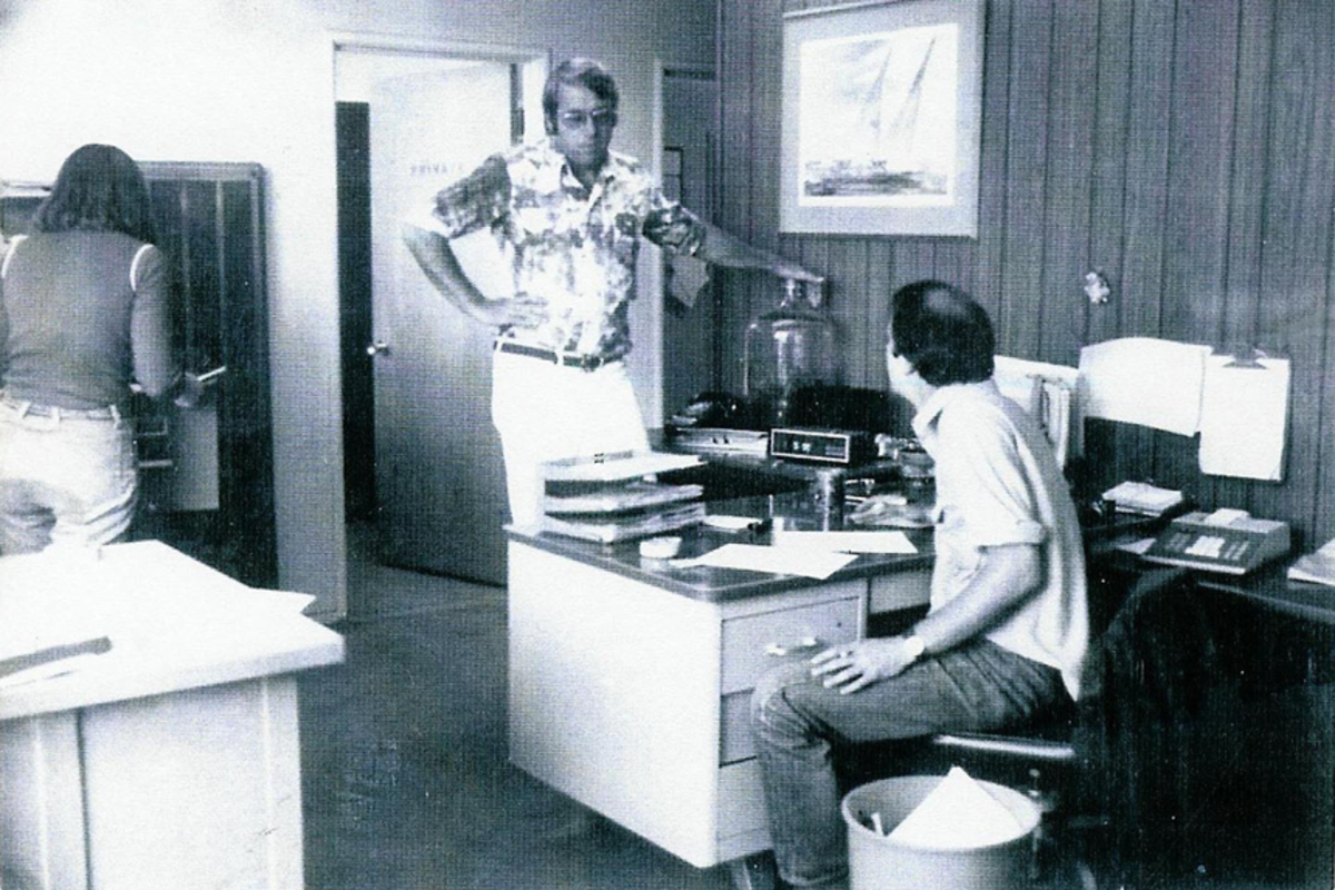 Selig (standing) and Aquistapace (seated) strategize in the company's early days.