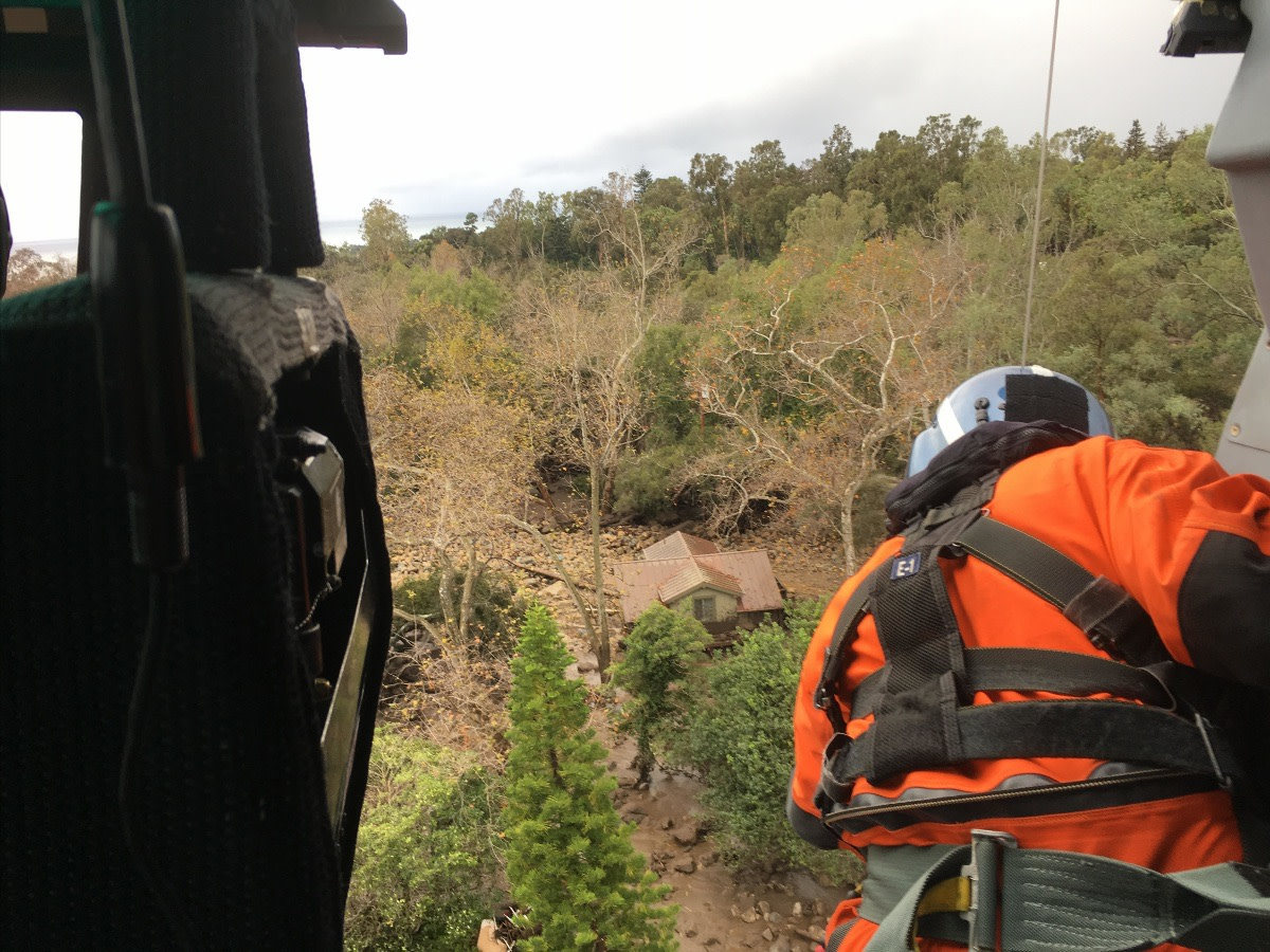A crew member looks down on a neighborhood affected by the Santa Barbara County mudslides in Santa Barbara, California, Jan. 9, 2018. (Photo by Petty Officer 3rd Class DaVonte Marrow, U.S. Coast Guard District 11 PADET Los Angeles)