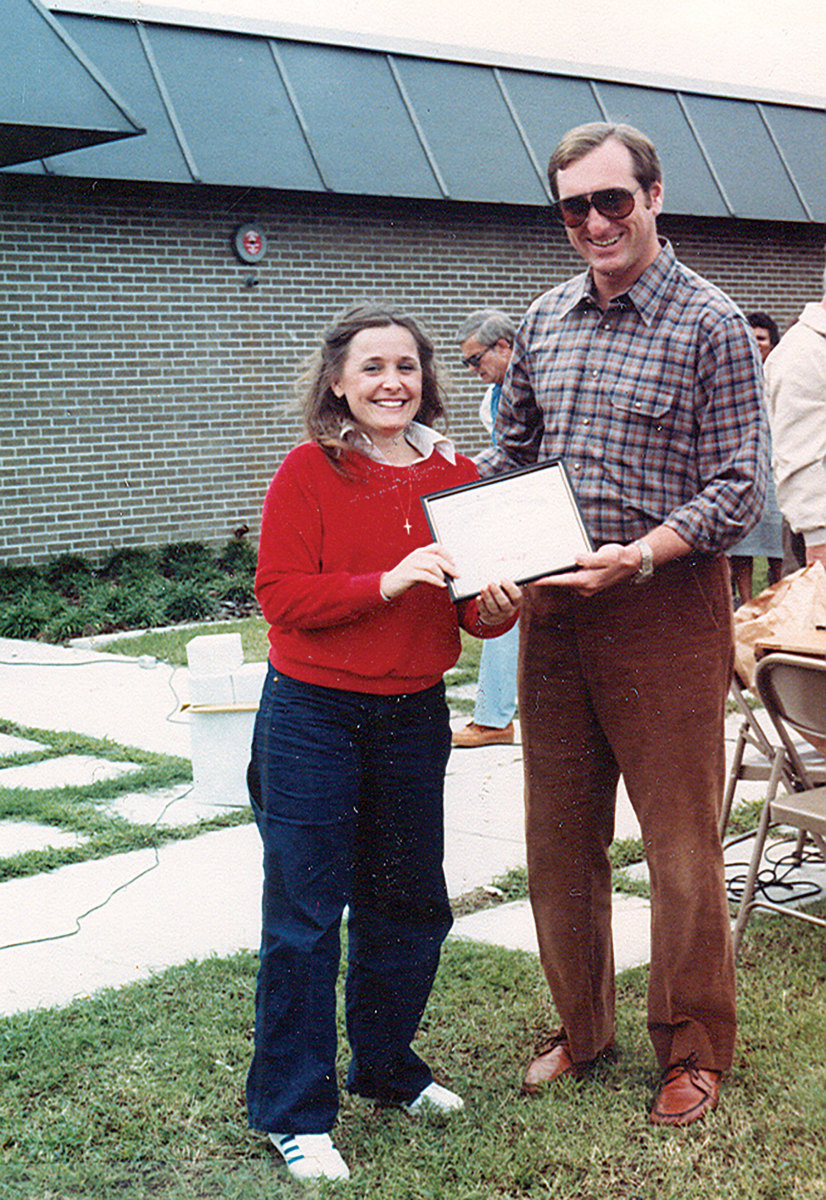 Grady-White founder Eddie Smith gives Car­­roll her five-year certificate in 1980.