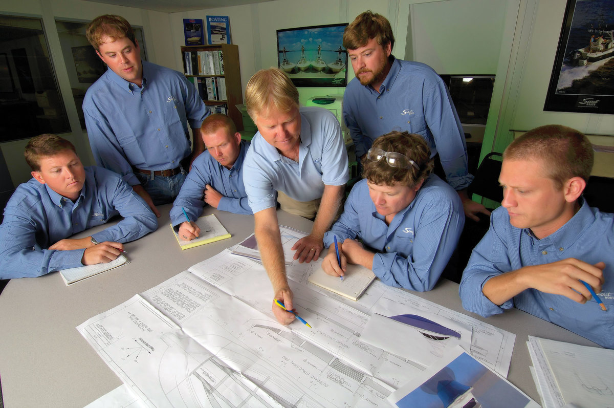 Steve Potts (center) works with the design team, including Stevie (seated, right of his dad).