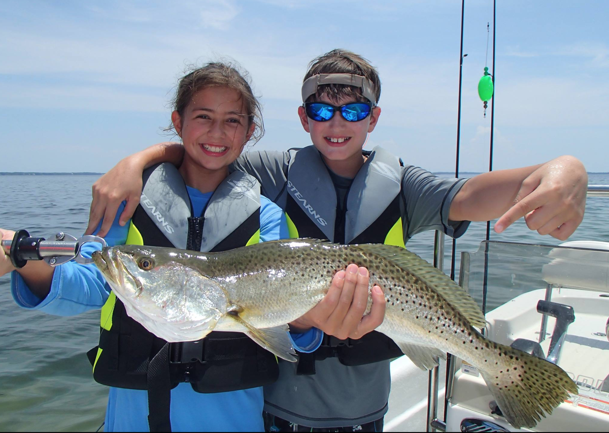 Lily Naylor adds a spotted seatrout to her Saltwater Fish Life List, with brother Peyton cheering her on. Photo by Jeff Naylor.