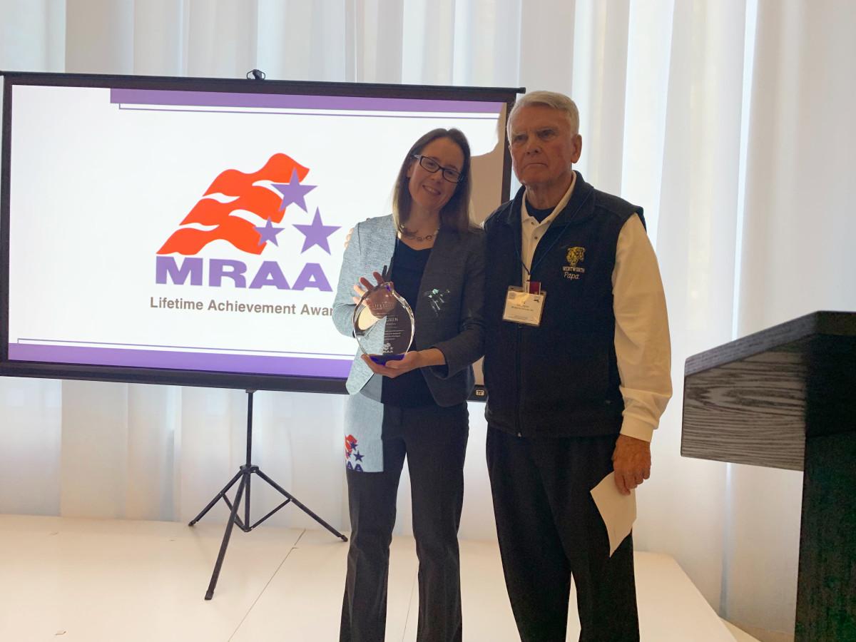 MRAA vice president Liz Walz presents Ed Lofgren of 3A Marine with a Lifetime Achievement Award.