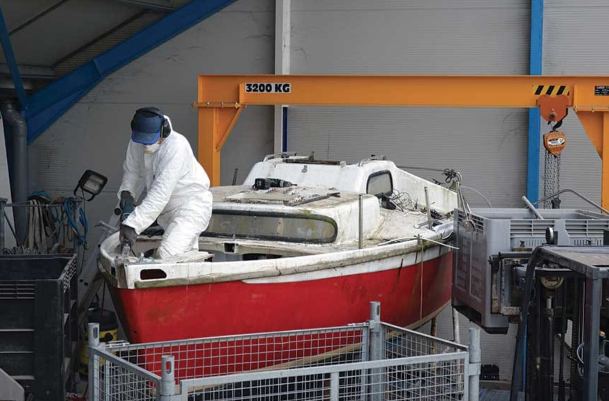 A boat in France being stripped of fixtures, wiring and tanks before the fiberglass hull is ground into chunks. Photo by APER.