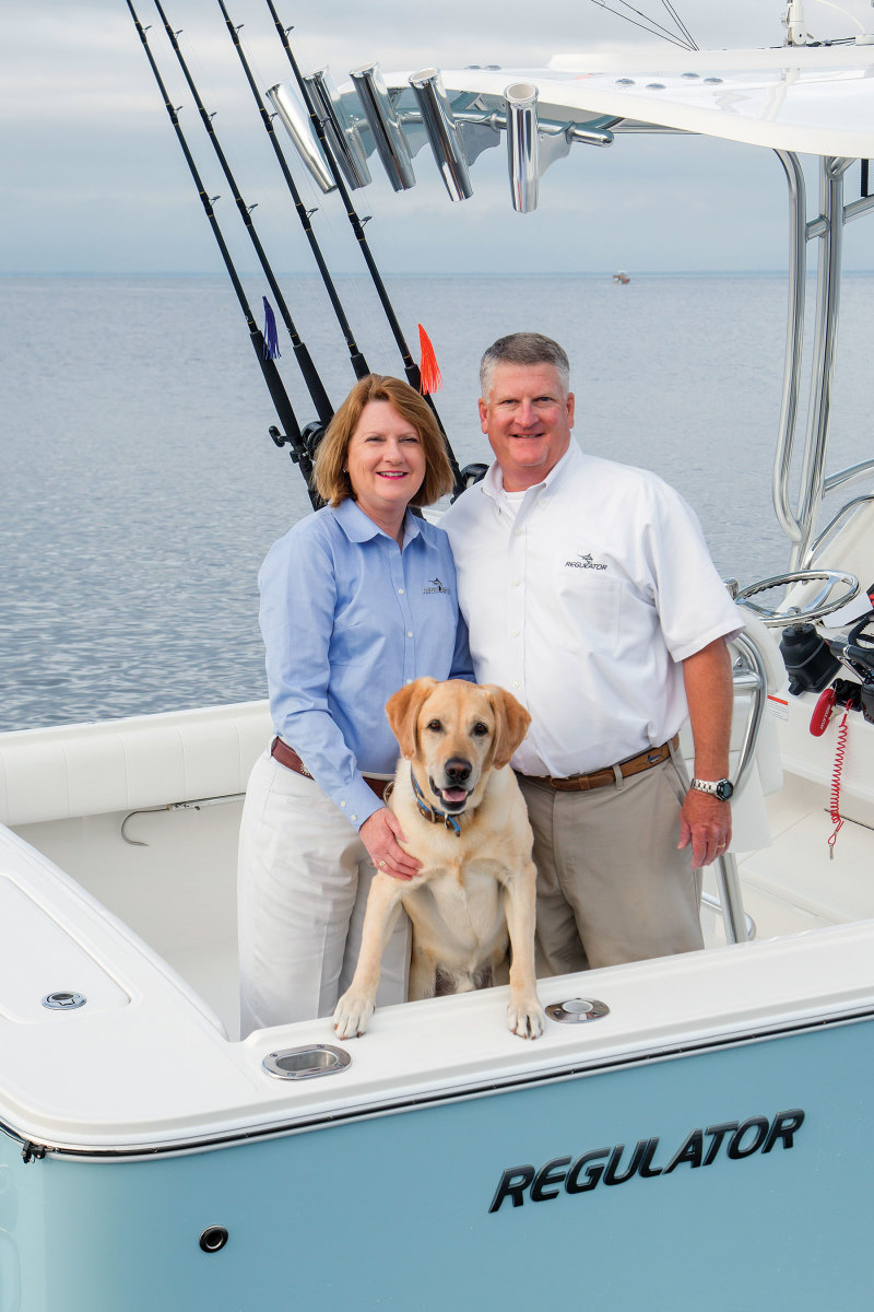 Regulator Marine co-captains and co-founders Joan and Owen Maxwell with first mate Buddy, their yellow Labrador.