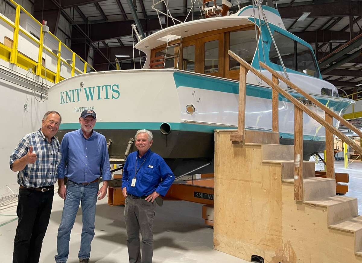 """Bass Pro founder Johnny Morris with 40-year Hatteras veterans Alden Harris and Bob Arthur in front of Knit Wits, the first Hatteras, which was launched in 1960 and hailed as the """"largest plastic production-built power cruiser."""""""