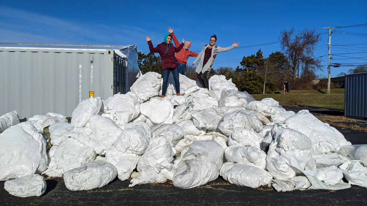 The Clean Ocean team on a pile of discarded shrinkwrap, ready for recycling.