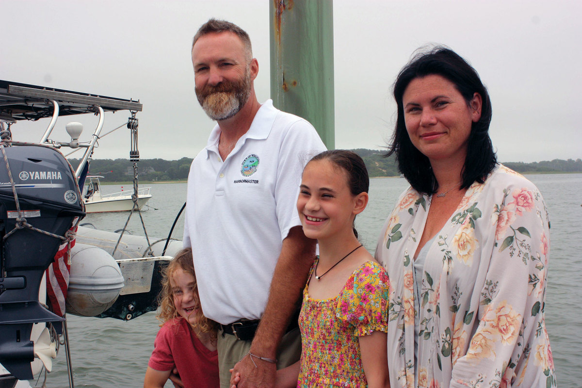 """The harbormaster of Wellfleet, Mass.,  Will Sullivan is shown here at the town dock with his two children and wife, Bri. """"Family is important to me,"""" he says."""