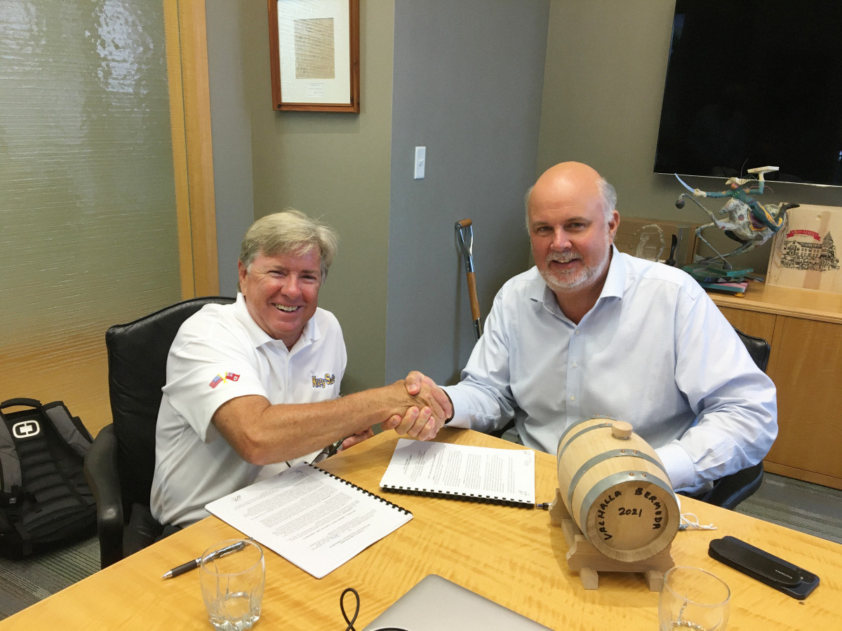 Waterfront Group president William Cox (right) gives Viking president and CEO Pat Healey a barrel of special-blend rum from the acclaimed Harry's Restaurant & Bar to seal the deal.