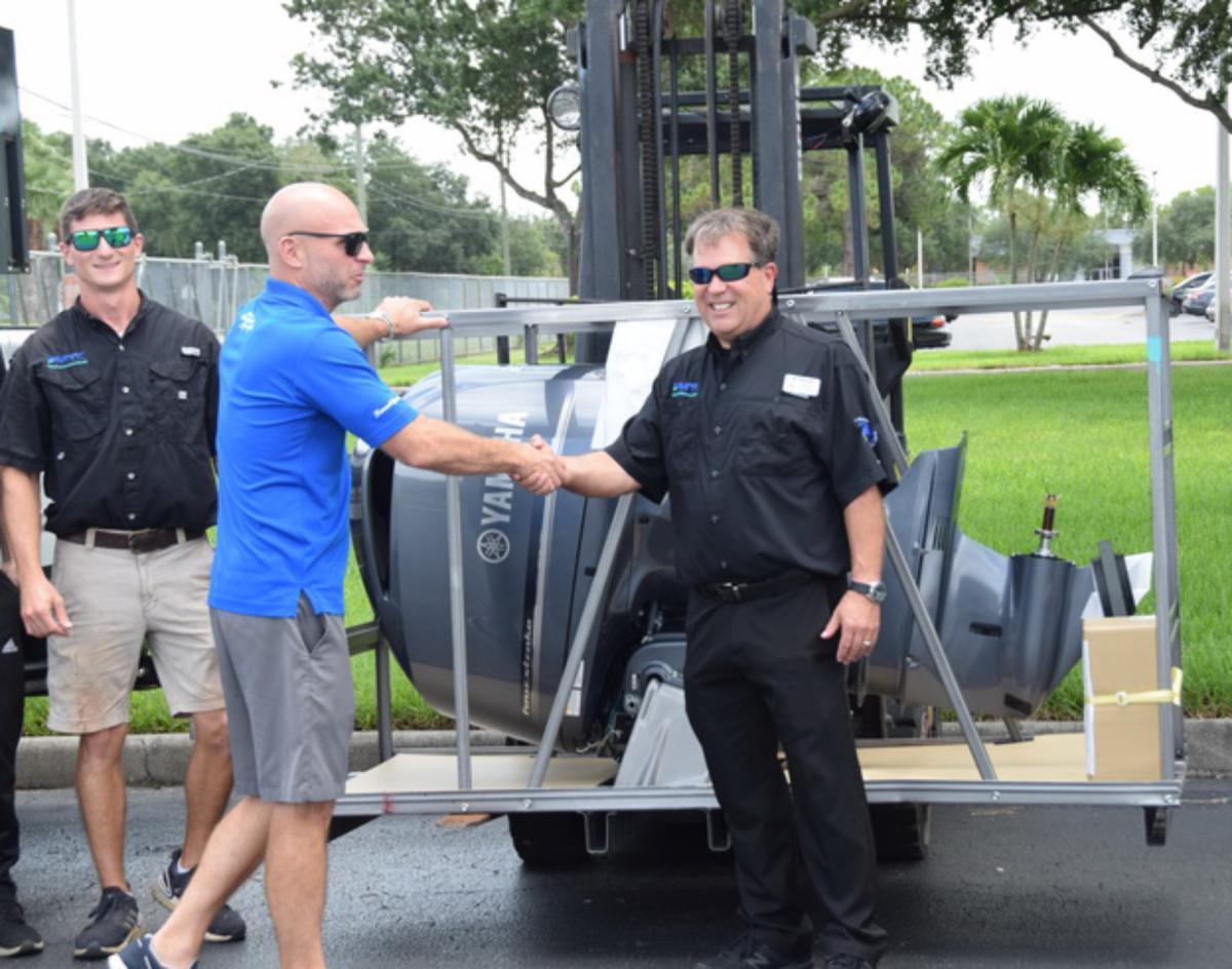 Joe Martin of Bonita Boat Center (right) with the donated F225.