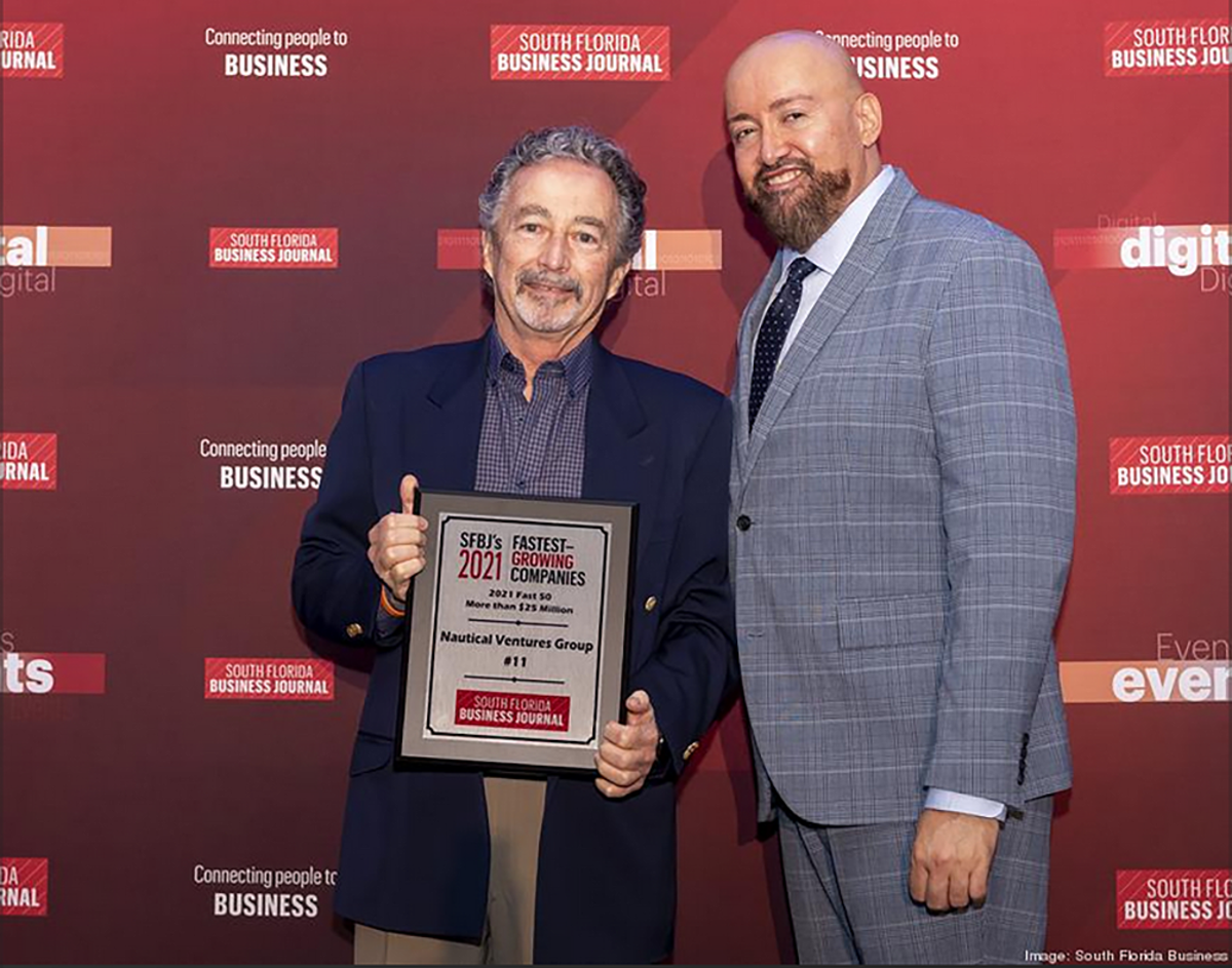 Nautical Ventures owner/CEO Roger Moore (left) accepts the recent South Florida business recognition.
